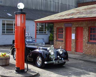 Here the Triumph Roadster is parked next to some period petrol pumps.