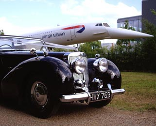 The Triumph Roadster next to the famous model of Concorde, formerly used to greet visitors to Heathrow.