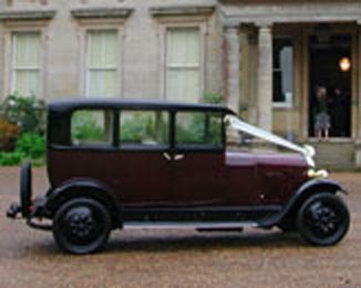 Dorothy, our burgundy Vintage Citroen outside a stately building.